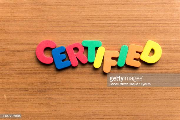 high angle view of colorful certified text on wooden table - medium group of objects stock pictures, royalty-free photos & images