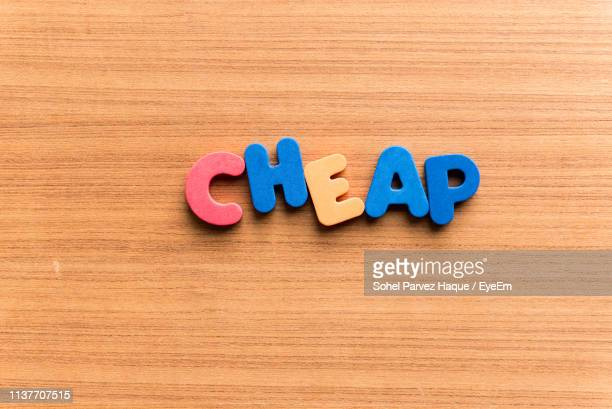 high angle view of colorful cheap text on wooden table - inexpensive stock photos and pictures