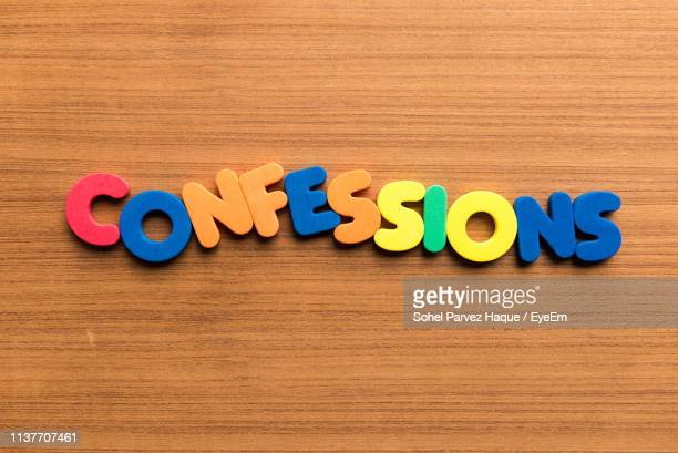 High Angle View Of Colorful Confessions Text On Wooden Table