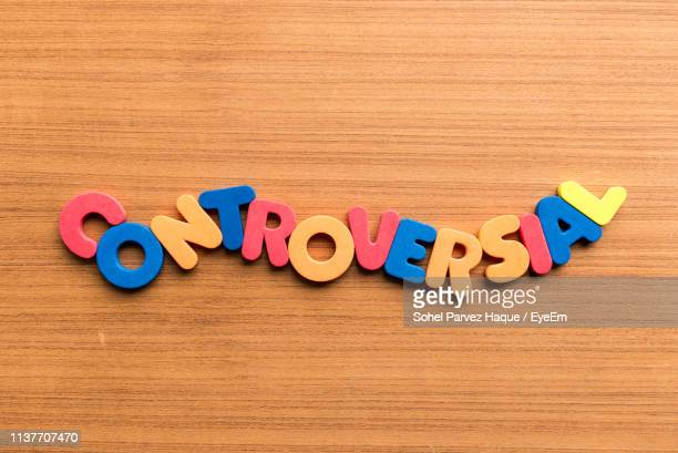 High Angle View Of Colorful Controversial Text On Wooden Table
