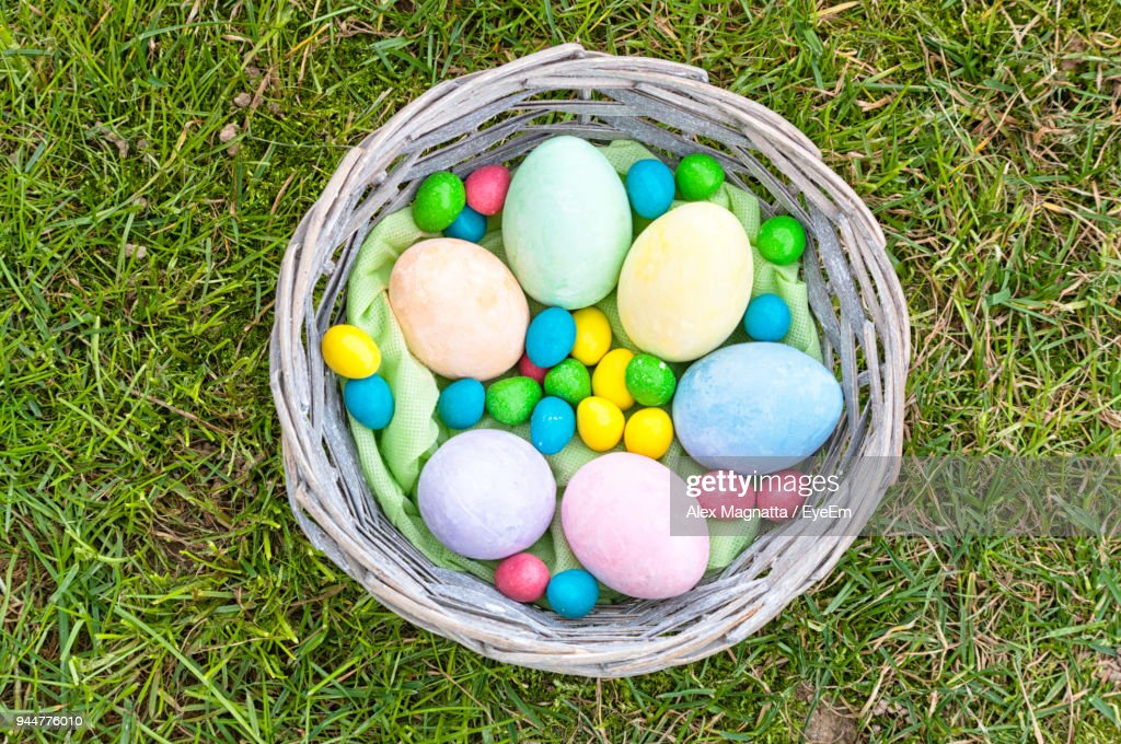 High Angle View Of Colorful Easter Eggs In Basket On Field : Stock Photo