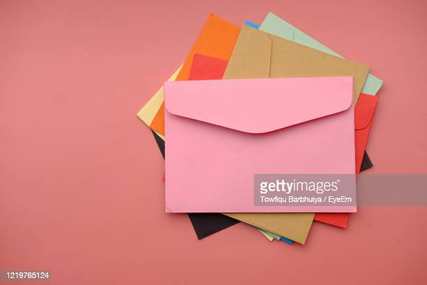 high angle view of colorful envelope pink background . - greeting card stock pictures, royalty-free photos & images