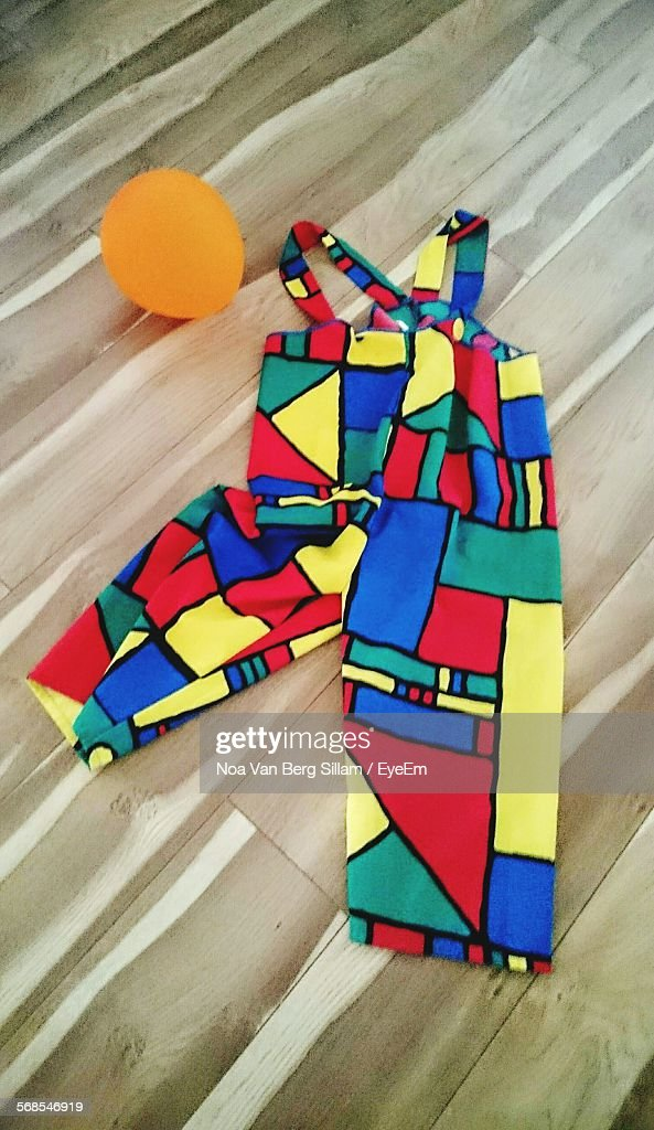 High Angle View Of Colorful Fabric And Orange Balloons On Floor At Home : Stock Photo