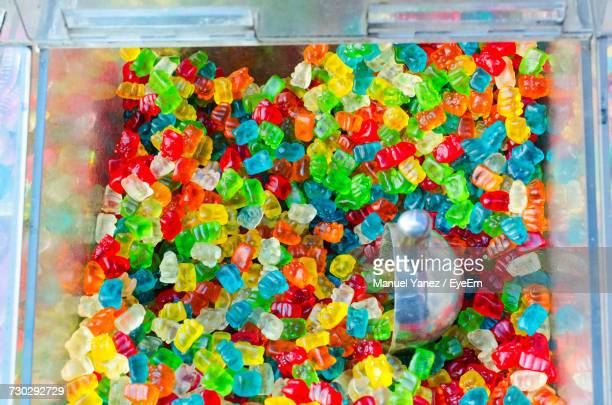 high angle view of colorful gummi bears in glass container for sale - gummi bears stock photos and pictures