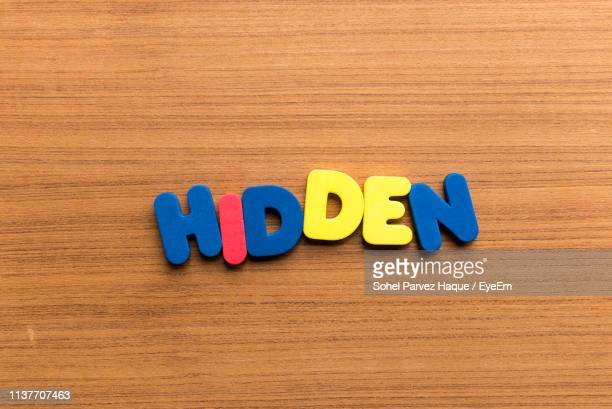 High Angle View Of Colorful Hidden Text On Wooden Table