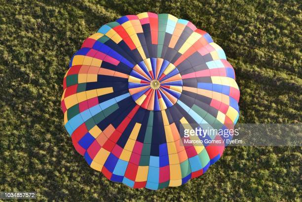 high angle view of colorful hot air balloon over landscape - fallschirm stock-fotos und bilder