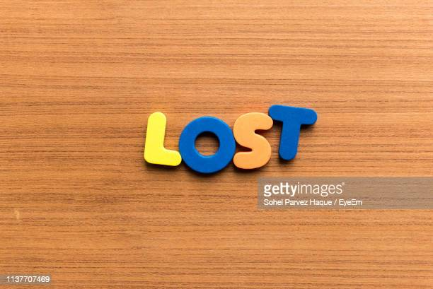 High Angle View Of Colorful Lost Text On Wooden Table