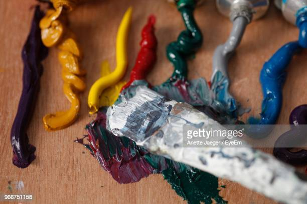 High Angle View Of Colorful Paints With Brush On Table At Workshop