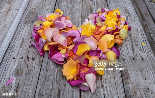 High Angle View Of Colorful Petals Arranged In Heart Shape On Wooden Table