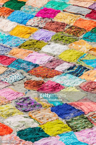 High angle view of colorful saris drying on flat ground