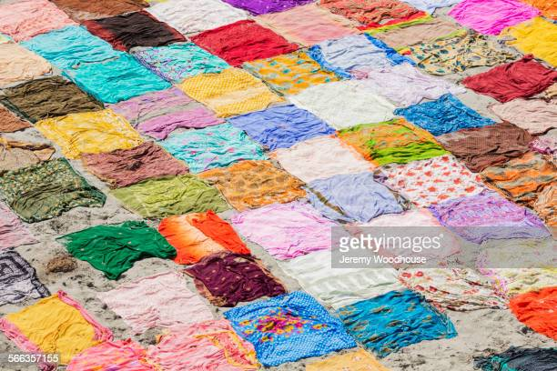 high angle view of colorful saris drying on flat ground - patchwork stock pictures, royalty-free photos & images