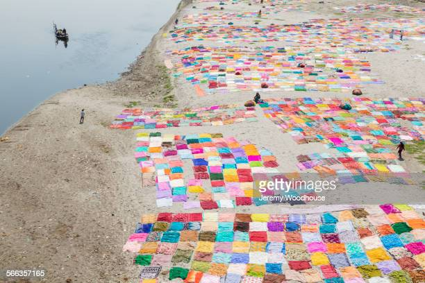 High angle view of colorful saris drying on flat riverbank