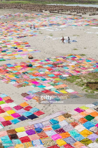 High angle view of colorful saris drying on riverbank