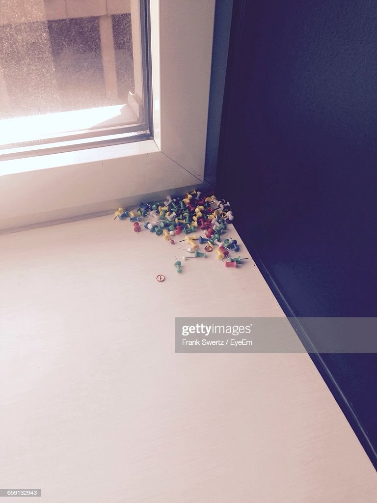 High Angle View Of Colorful Thumbtacks By Window : Stock-Foto