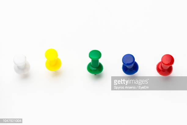 high angle view of colorful thumbtacks over white background - push pin stock pictures, royalty-free photos & images