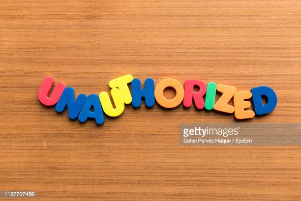 High Angle View Of Colorful Unauthorized Text On Wooden Table