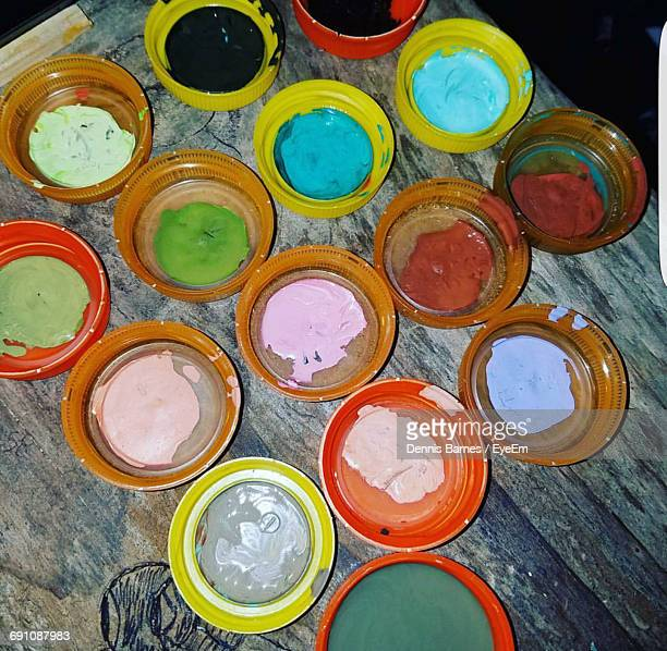 High Angle View Of Colorful Watercolor Paints On Lids Over Wooden Table