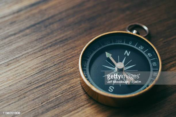 high angle view of compass on table - compass stock pictures, royalty-free photos & images