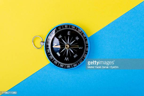 high angle view of compass on two tone background - compass stock pictures, royalty-free photos & images