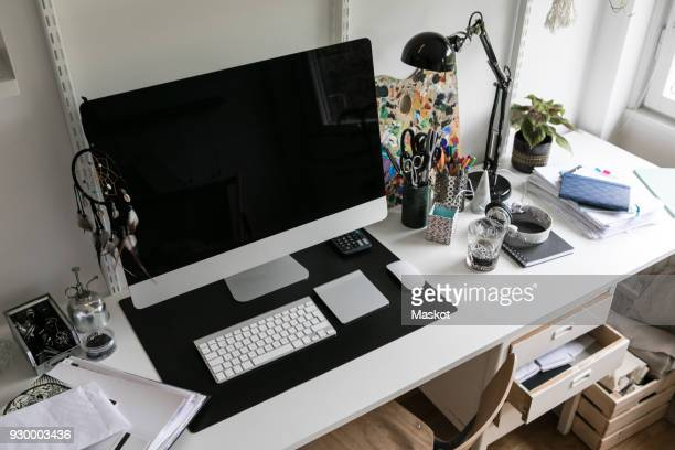 High angle view of computer with office supplies on desk at home