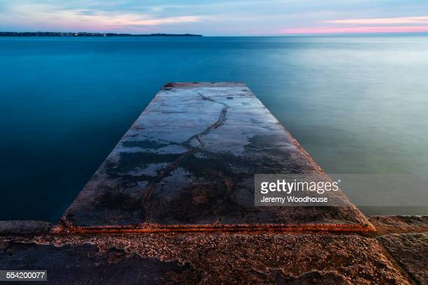 High angle view of concrete jetty over still ocean