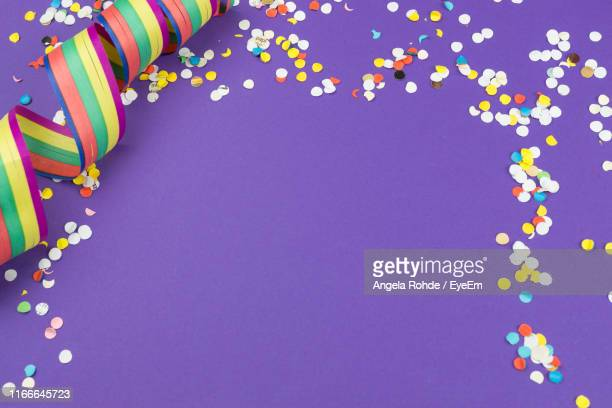 high angle view of confetti and streamer on purple background - streamer stock pictures, royalty-free photos & images