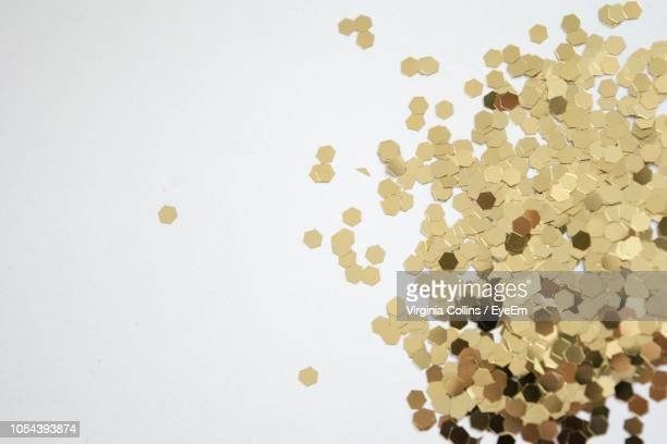 high angle view of confetti over white background - gold confetti stock photos and pictures