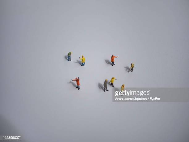 high angle view of construction worker figurines on gray background - human representation stock pictures, royalty-free photos & images