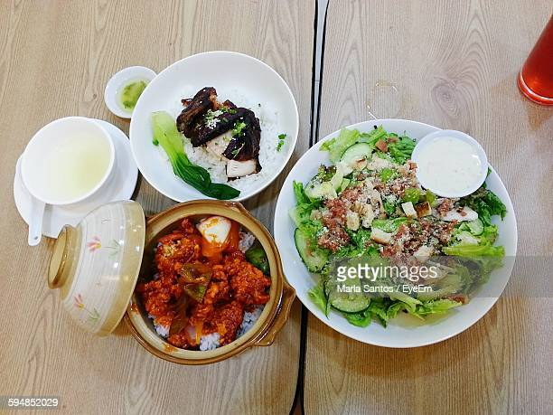 High Angle View Of Cooked Chicken With Rice And Salad On Table