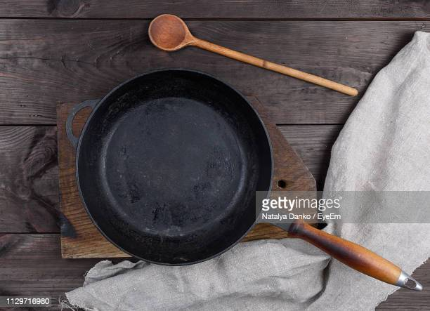 high angle view of cooking pan with spoon and napkin on wooden table - frying pan stock pictures, royalty-free photos & images
