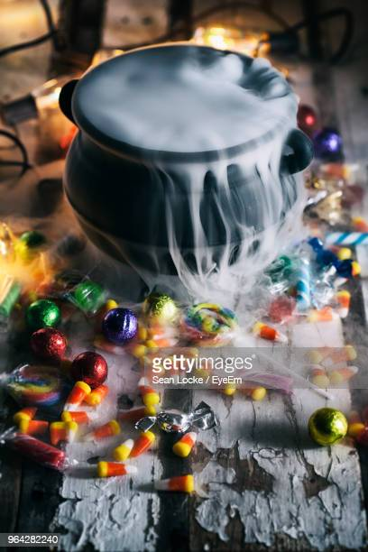 high angle view of cooking pot with smoke amidst scattered candies on table during halloween - halloween candy stock photos and pictures
