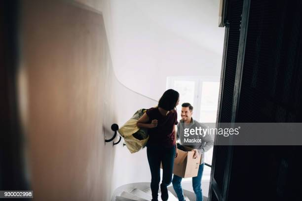 high angle view of couple carrying bag and box while climbing up steps - physical activity stock pictures, royalty-free photos & images