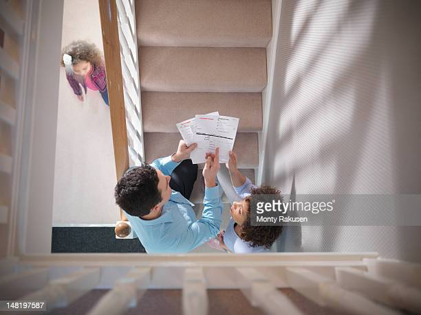 High angle view of couple discussing energy fuel bills on staircase of home