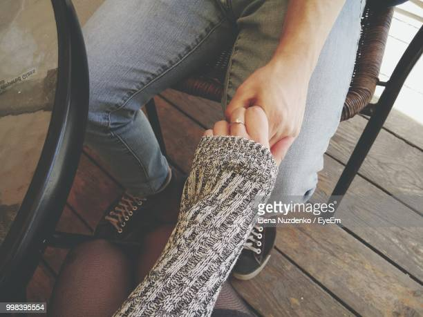 high angle view of couple holding hands while sitting at table - parte inferior imagens e fotografias de stock
