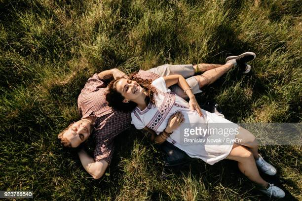 high angle view of couple lying down on field - lying down stock-fotos und bilder
