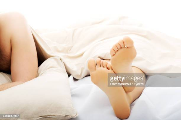 High Angle View Of Couple Lying On Bed At Home
