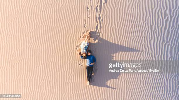 high angle view of couple lying on sand at desert - chihuahua desert stock pictures, royalty-free photos & images