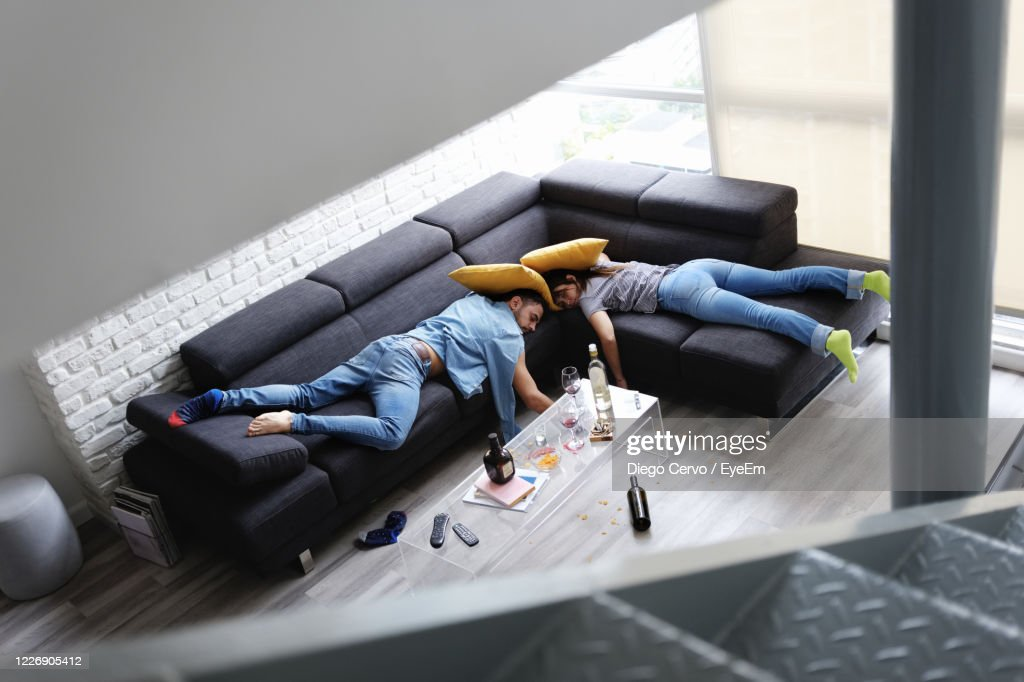 High Angle View Of Couple Lying On Sofa After Party At Home : Stock Photo