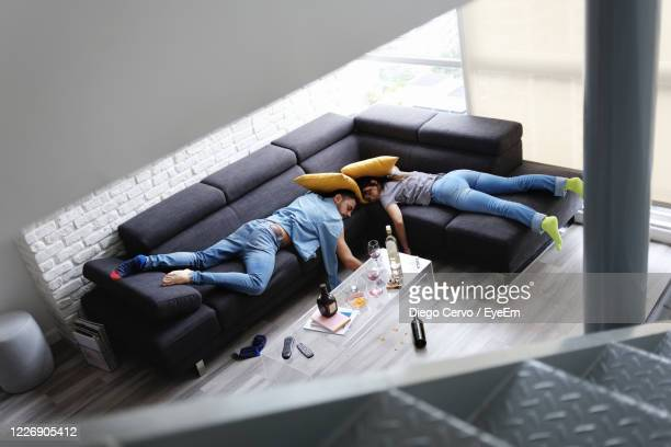 high angle view of couple lying on sofa after party at home - hangover after party stock pictures, royalty-free photos & images