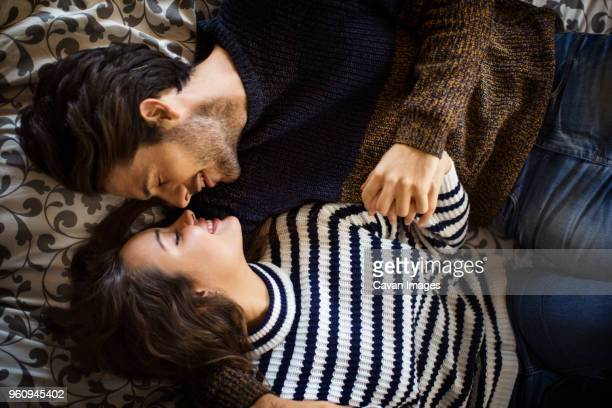 High angle view of couple lying with holding hands on alcove window seat at home