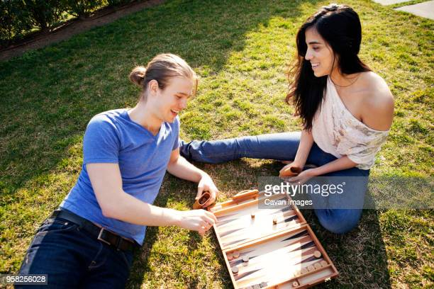 High angle view of couple playing Backgammon game at grassy field