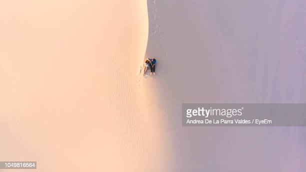 high angle view of couple sitting on sand at desert - chihuahua desert stock pictures, royalty-free photos & images