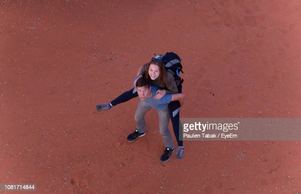 High Angle View Of Couple Standing On Sand