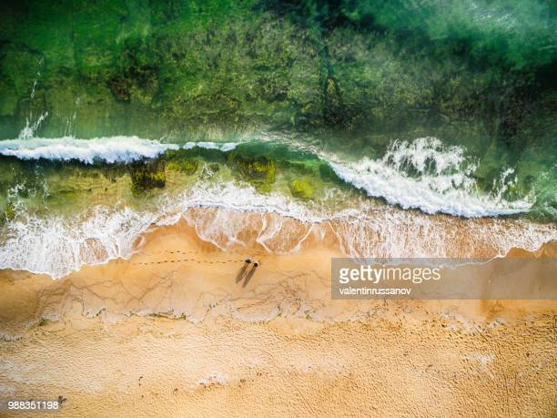 high angle view of couple standing on the beach - riva dell'acqua foto e immagini stock