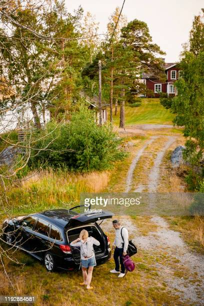 high angle view of couple unloading luggage from car trunk during vacation - landfahrzeug stock-fotos und bilder
