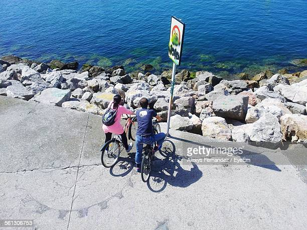High Angle View Of Couple With Bicycle On Pier With Groyne Looking At Water