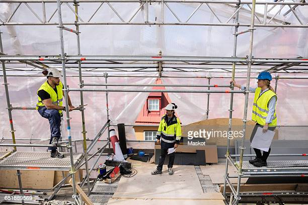 High angle view of coworkers listening to manager while standing in construction site