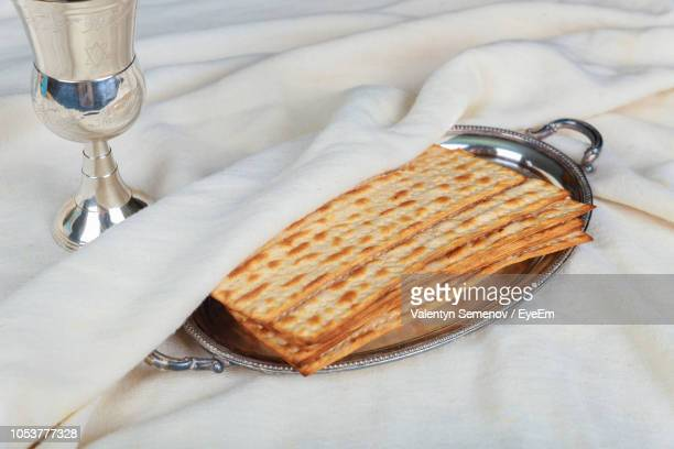 high angle view of crackers in plate by chalice on textile - matzah stock pictures, royalty-free photos & images