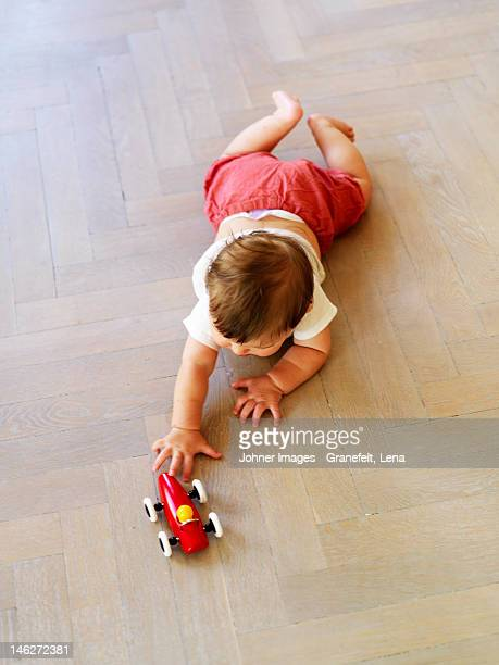 High angle view of crawling boy playing with toy car
