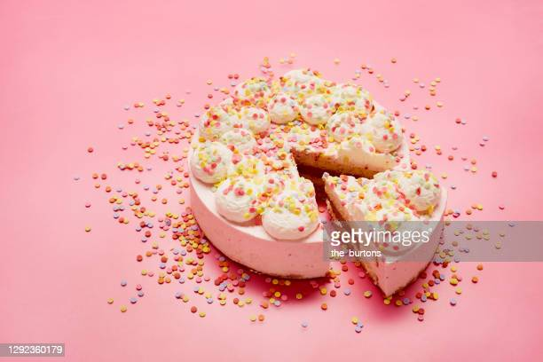 high angle view of cream cake and colourful sugar sprinkles on pink background - cake stock pictures, royalty-free photos & images